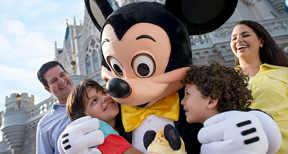 Mickey hugs 2 boys as their parents look on, in front of Cinderella's castle at Magic Kingdom park