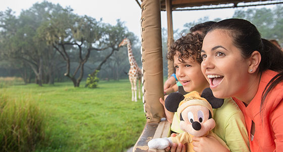 Excited mother and son in a safari vehicle see a giraffe on the grasslands of Disney Animal Kingdom