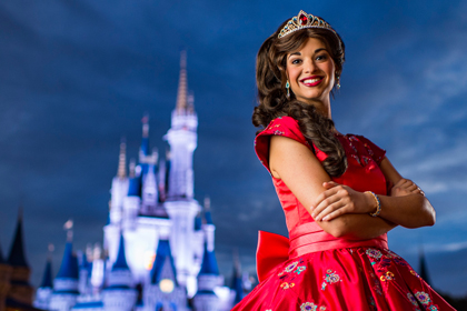 Princess Elena of Avalor wearing a jeweled tiara stands in front of Cinderella Castle at night