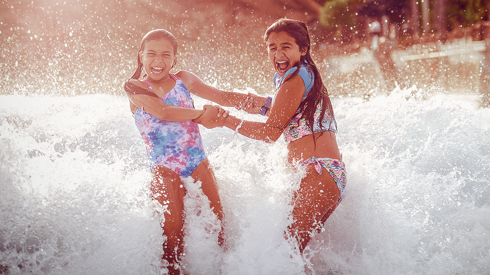 Two girls play in the shallow end of a wave pool