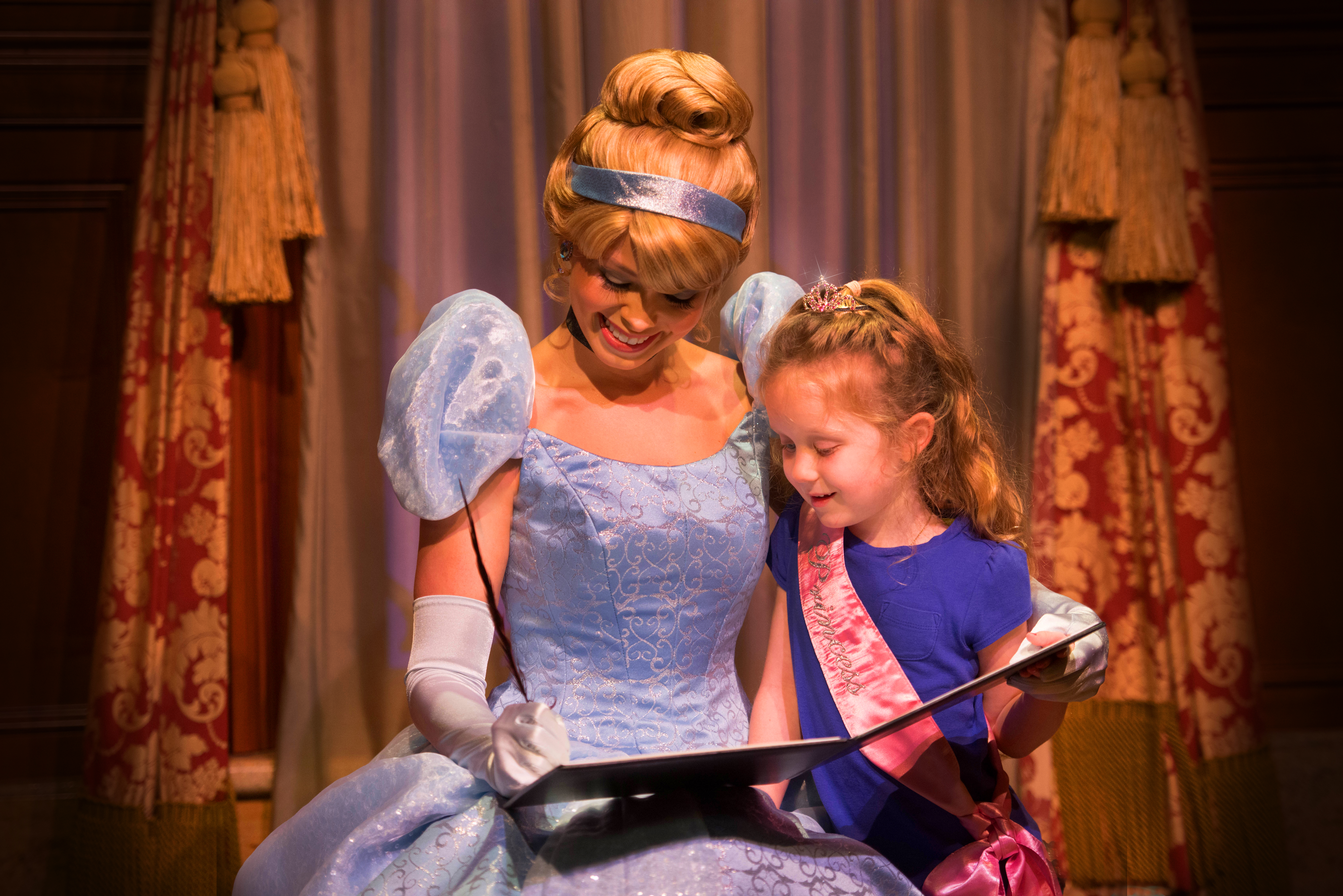 A girl wearing a tiara and princess sash watches excitedly as Cinderella signs her royal proclamation