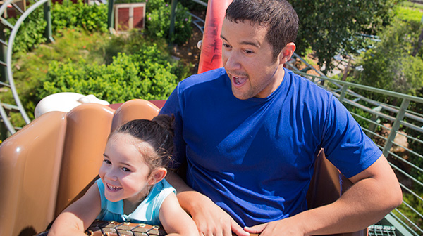 A father and daughter smile in excitement as they ride a roller coaster