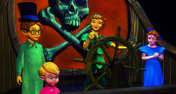 Peter Pan and the Darling children stand at the helm of a pirate ship