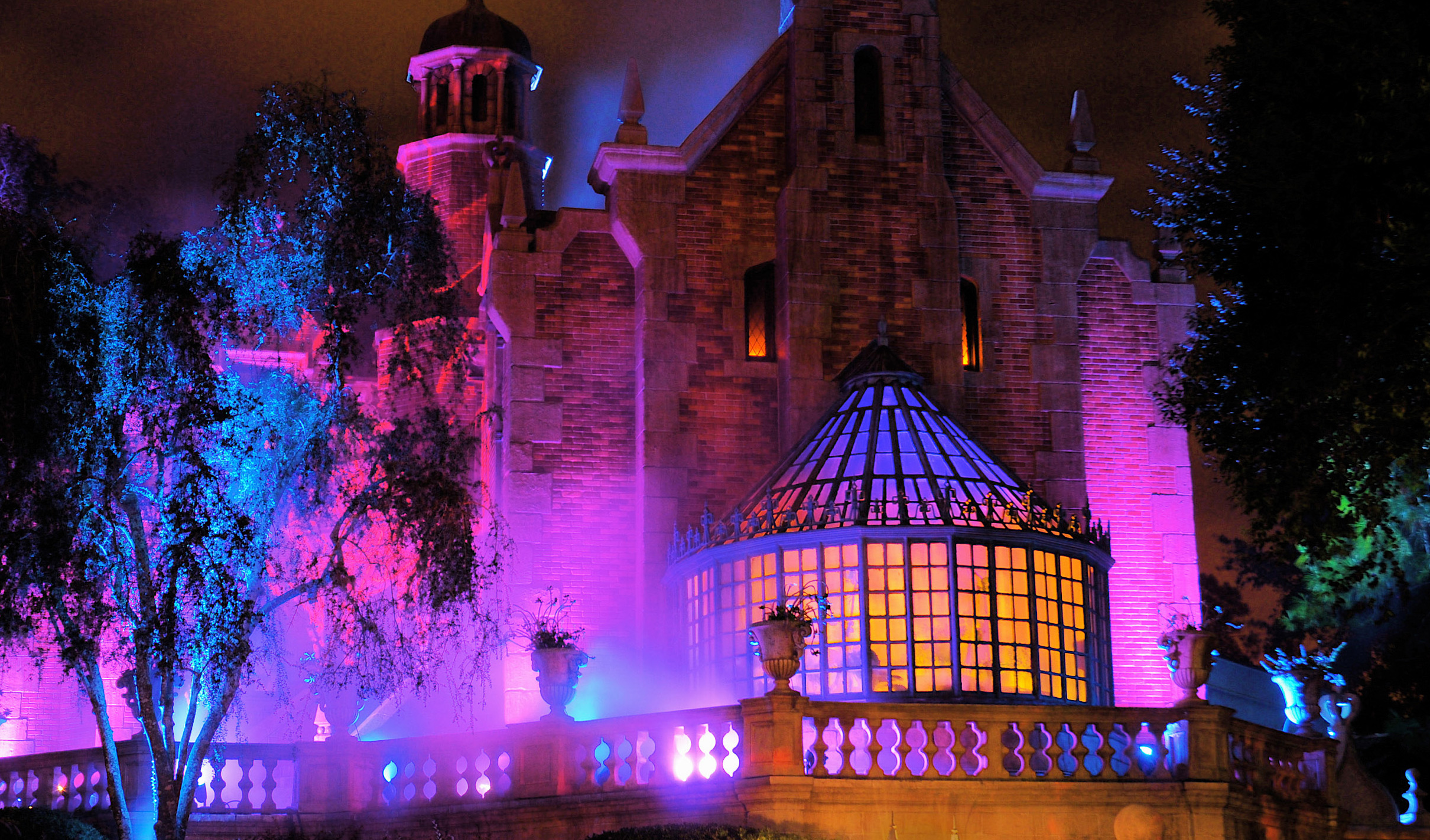 Mist rises from the Haunted Mansion as its exterior illuminates in the evening at Magic Kingdom park