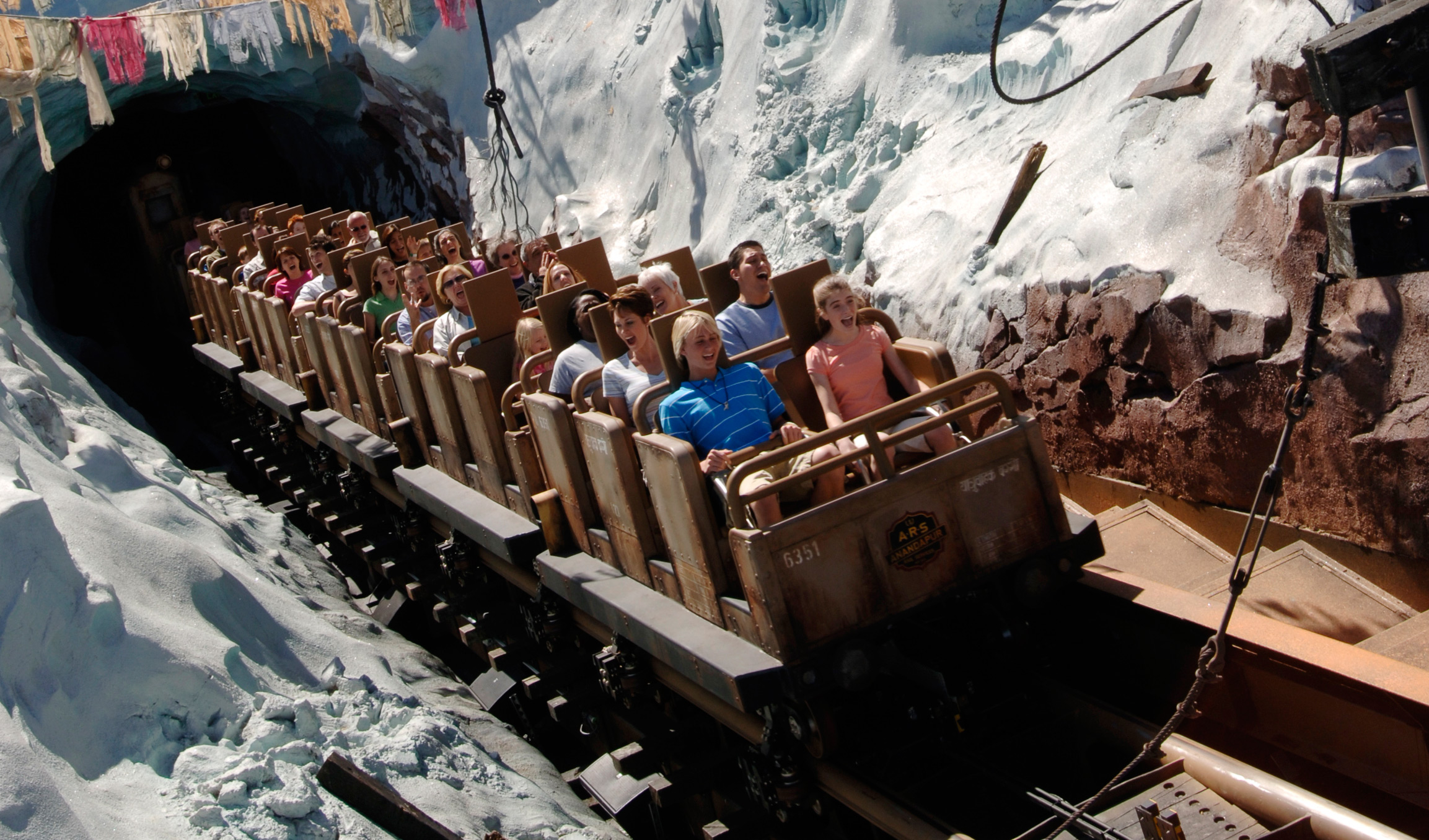 Huéspedes descienden a toda velocidad por una empinada colina en Expedition Everest – Legend of the Forbidden Mountain