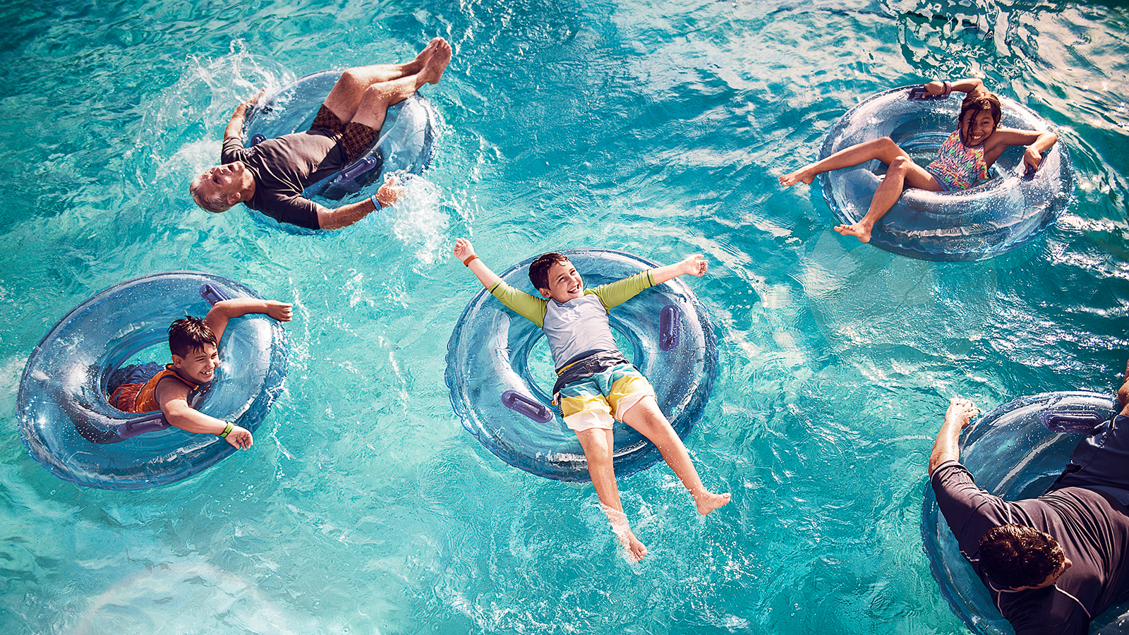 Guests of all ages splashing about in a pool while lounging on inner tubes at a Disney Resort hotel