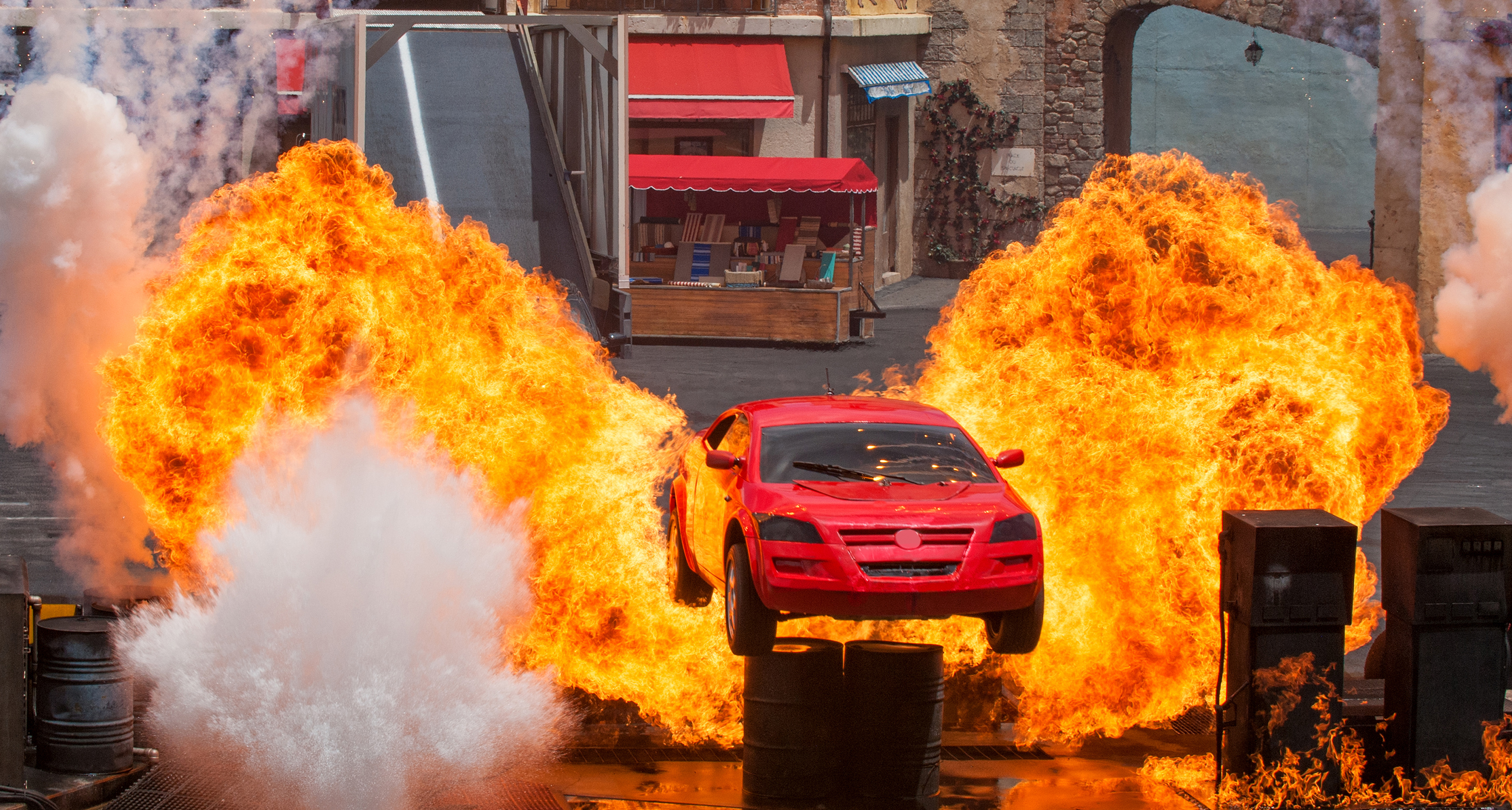 Explosions nearly engulf a car as it launches into the air at Lights, Motors, Action! Extreme Stunt Show