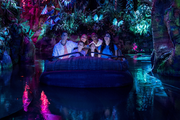 Guests aboard a reed boat drifting into a bioluminescent rainforest during the Na'vi River Journey