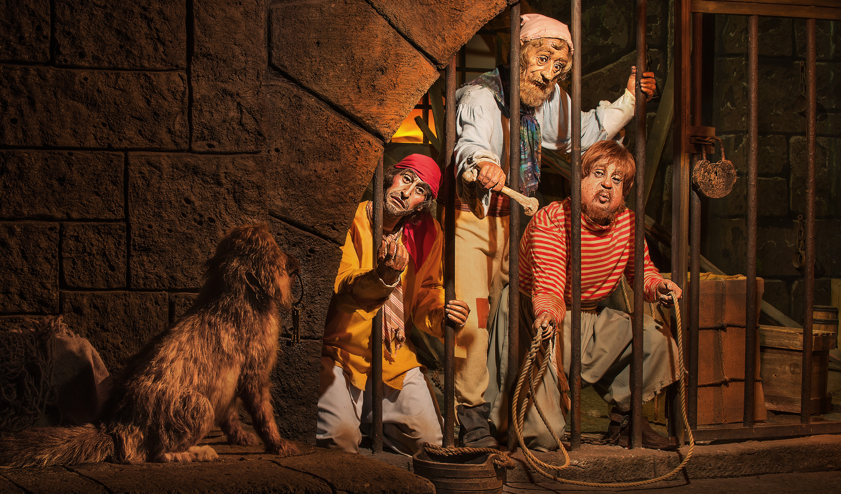 Jailed pirates attempt to coerce a keys from a dog on Pirates of the Caribbean at Magic Kingdom park