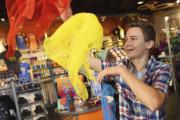 A young male Guest shopping for La Nouba by Cirque du Soleil merchandise at a store in Disney Springs