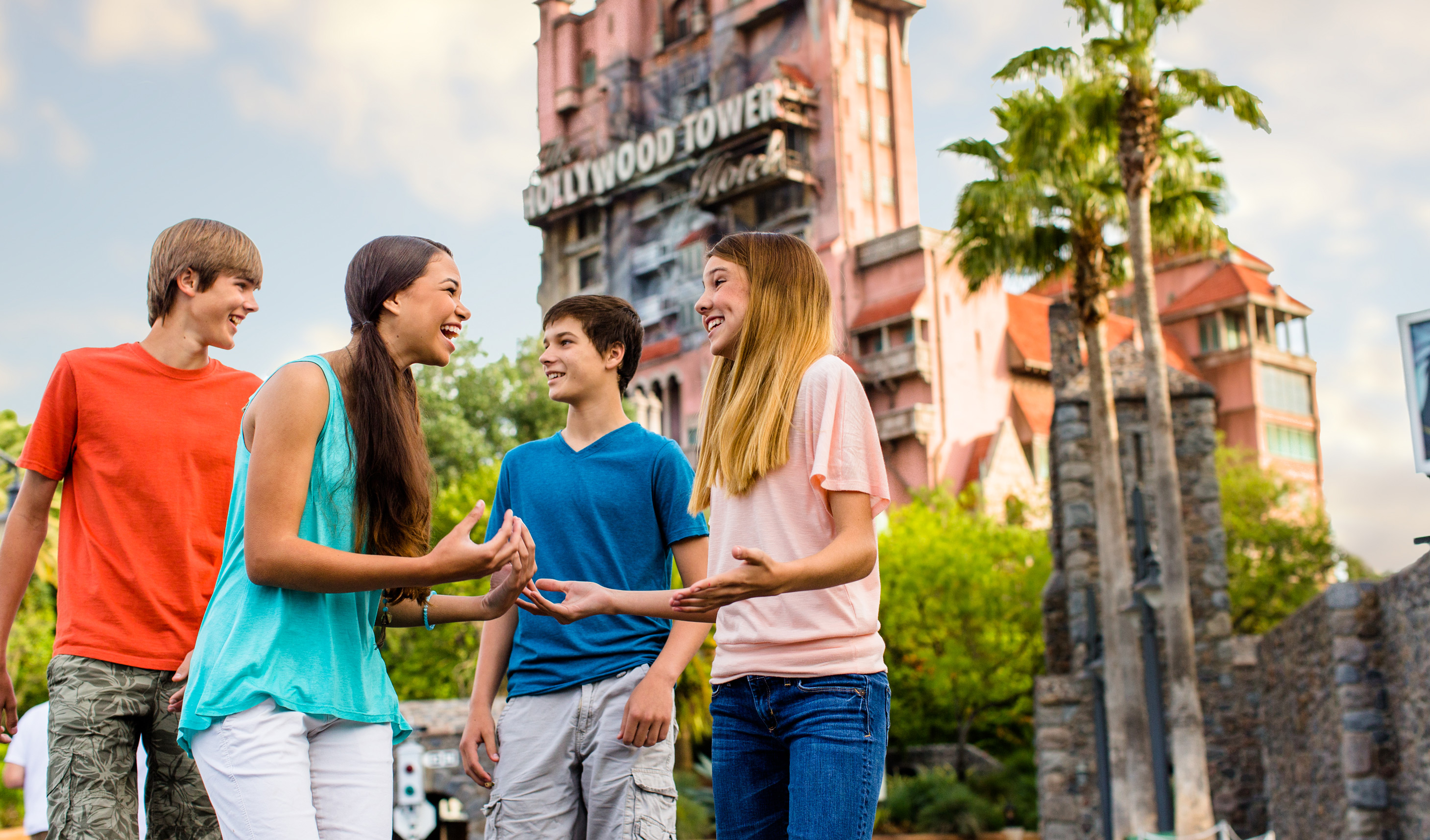 A group of young Guests laugh excitedly with one another outside The Twilight Zone Tower of Terror