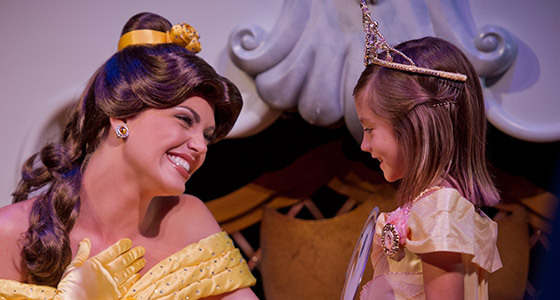 Belle smiles at a little girl wearing a Belle costume.