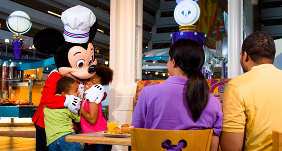 Chef Mickey hugs a young boy and girl as their parents look on during a Character dining experience