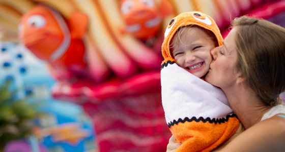 A young daughter smiling while wearing a Nemo-themed towel as her mother kisses her on the cheek