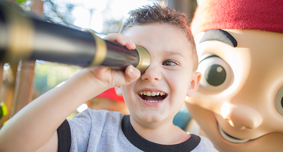 A preschool-aged boy looking through a spyglass is joined by Jake of Jake and the Never Land Pirates