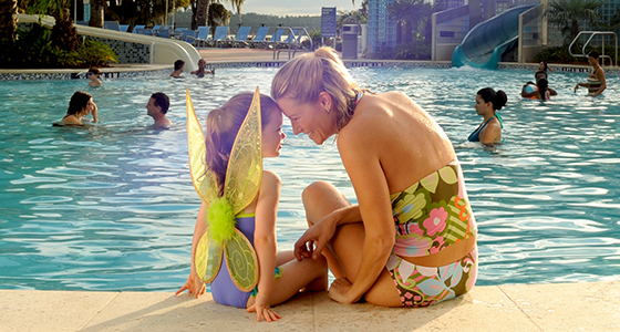 A mother touches foreheads with her preschool-aged daughter while sitting by a Disney-themed pool