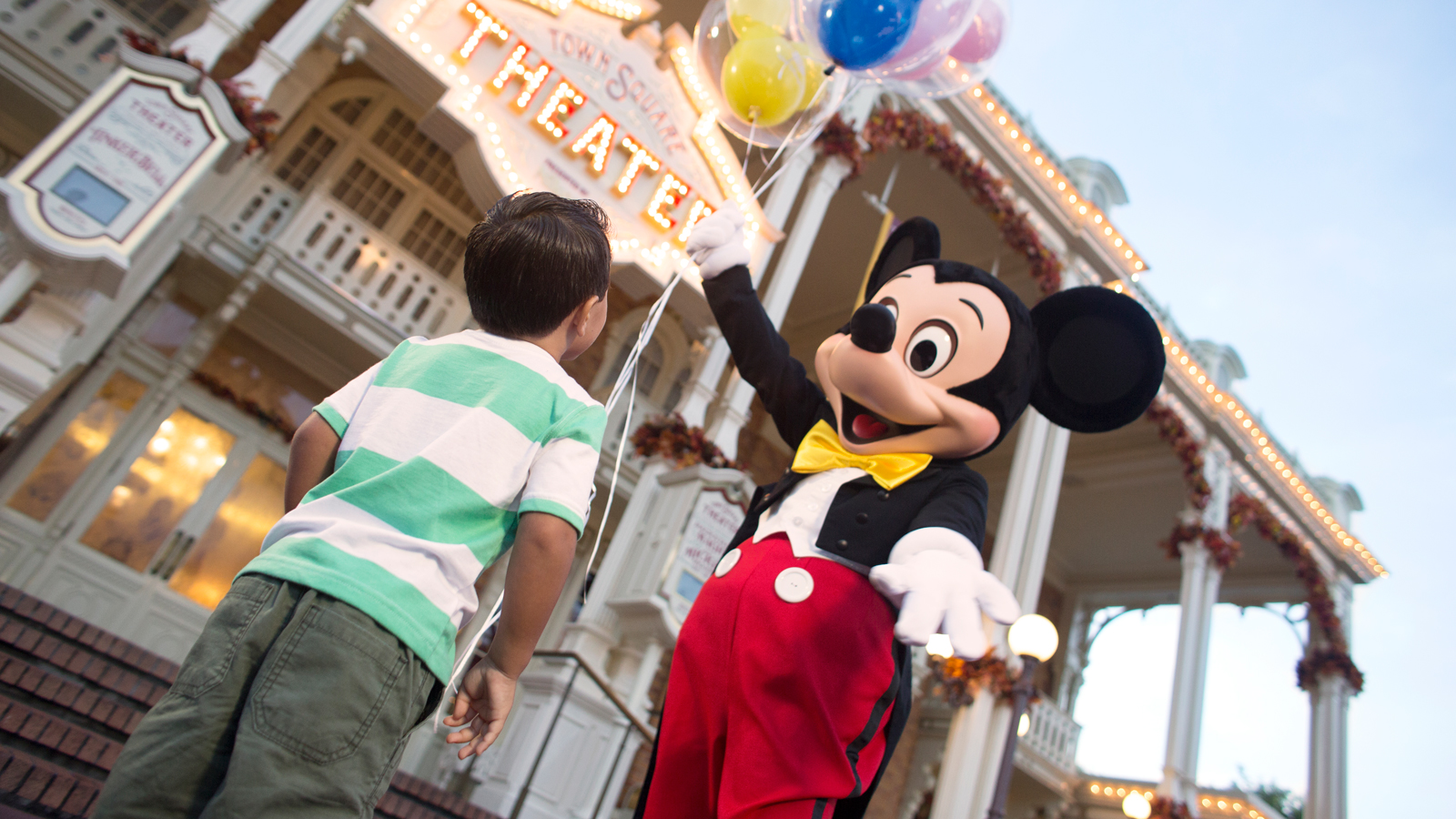 Mickey Mouse presents preschool boy with balloons in front of Town Square Theater
