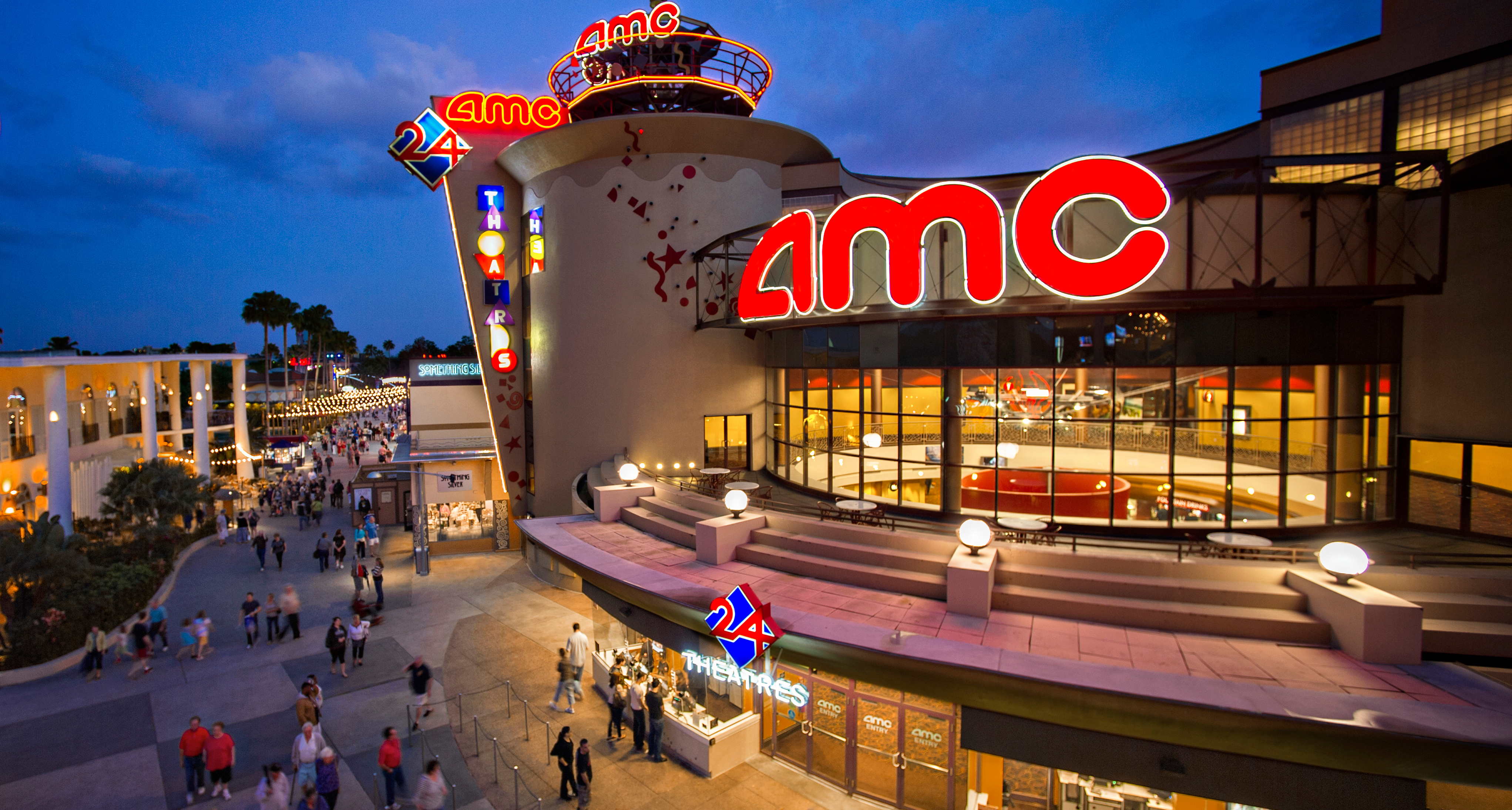 Bright lights illuminate the evening as Guests walk outside AMC Disney Springs 24 Dine-In Theater