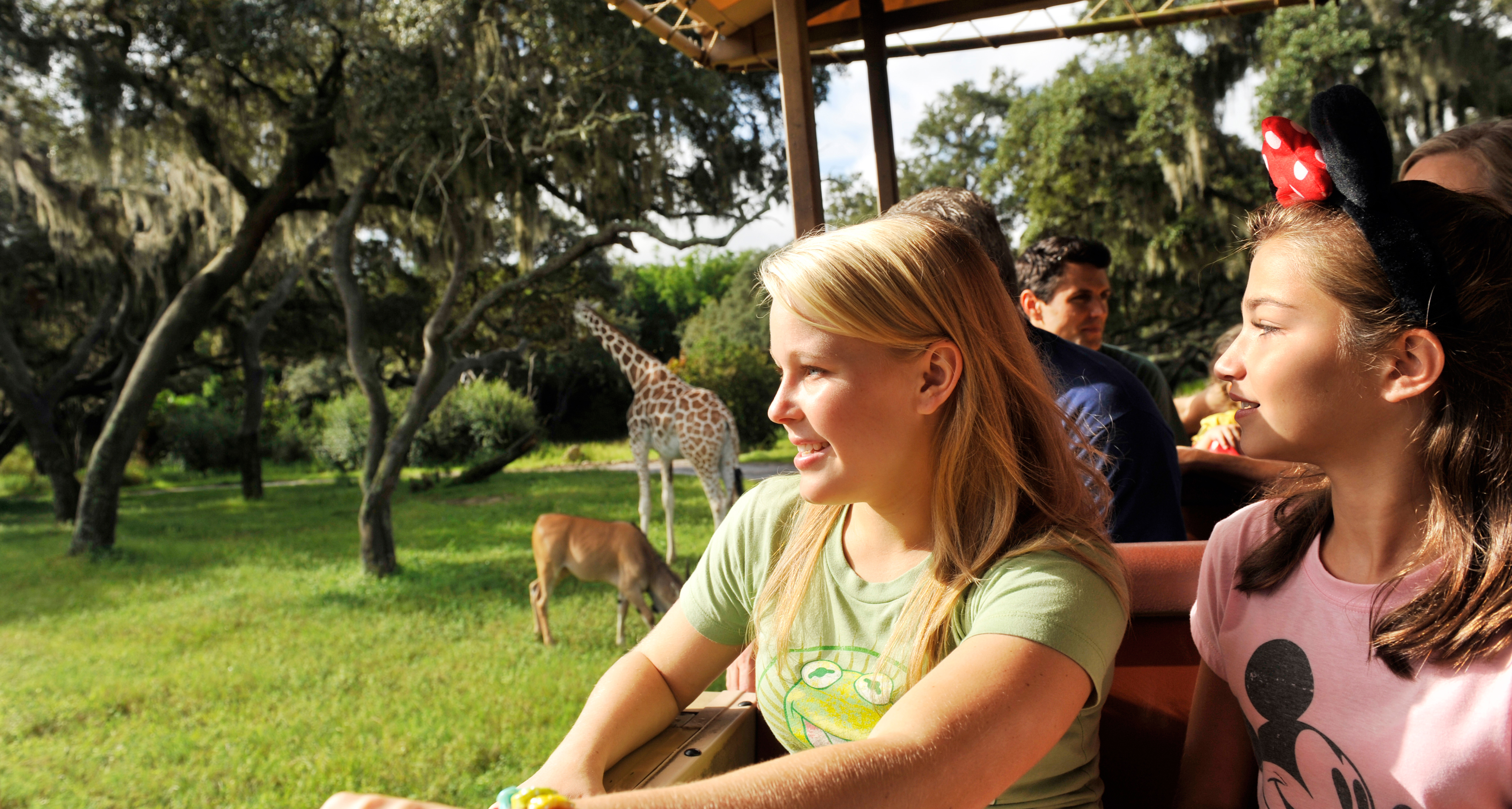 Young Guests watch in wonder while riding through the lush Savanna setting on Kilimanjaro Safaris