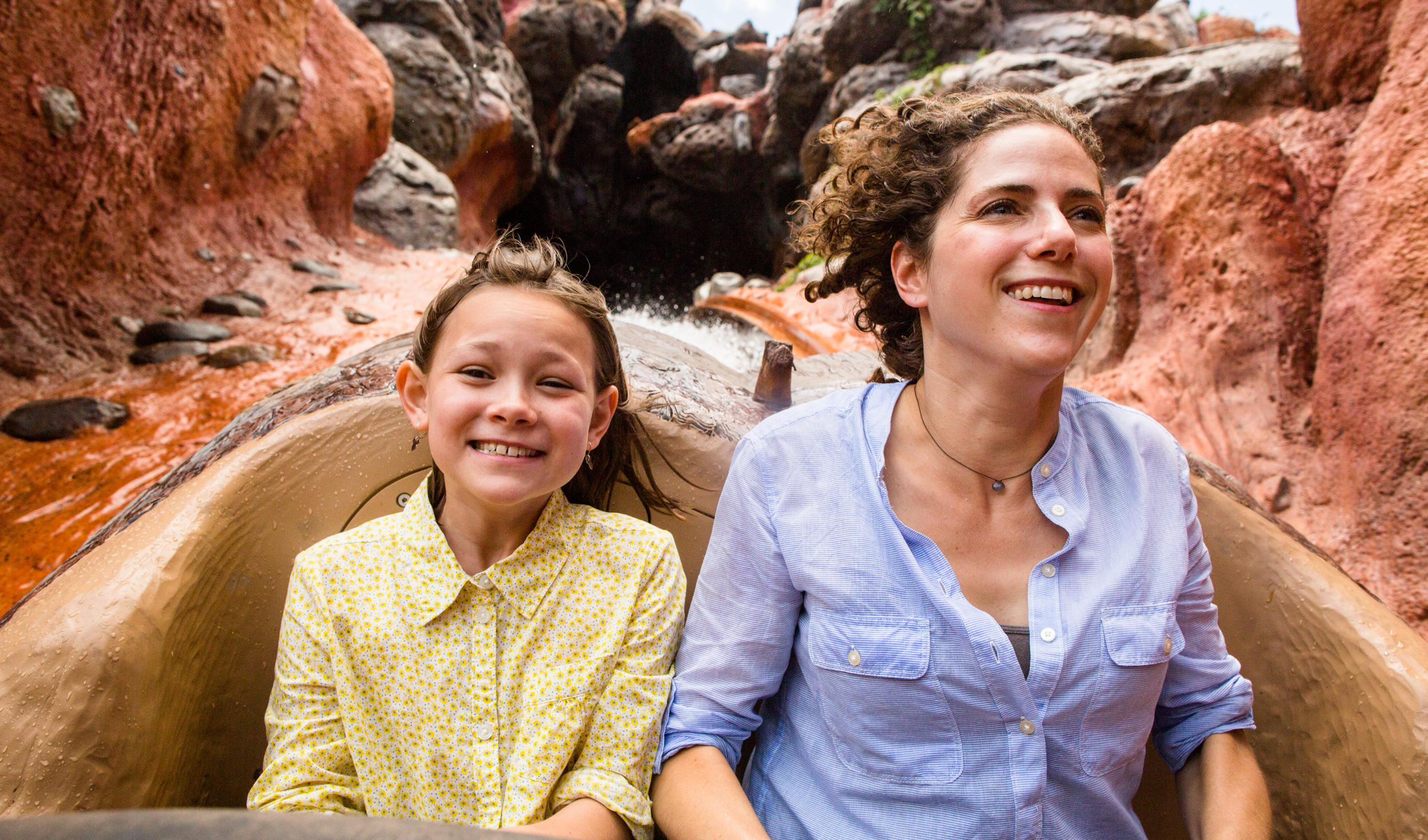 A mother and child smile while riding in a hollowed-out log on Splash Mountain at Magic Kingdom park