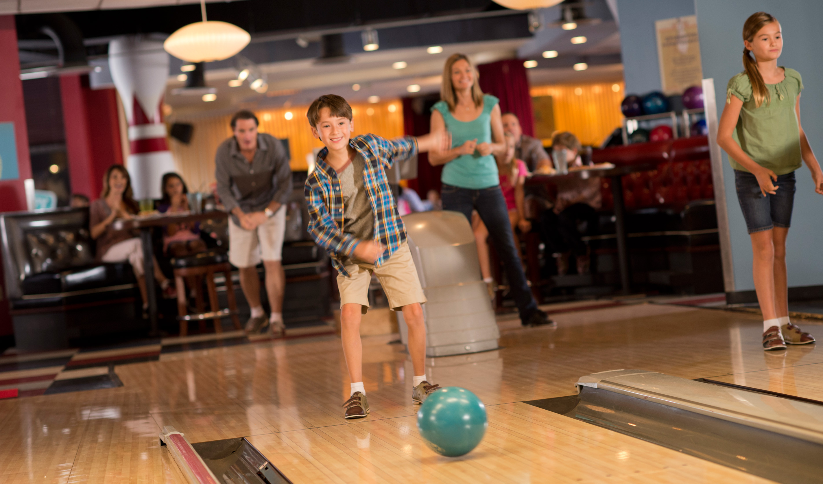A boy and his family watch in anticipation while he tosses a bowling ball at Splitsville Luxury Lanes