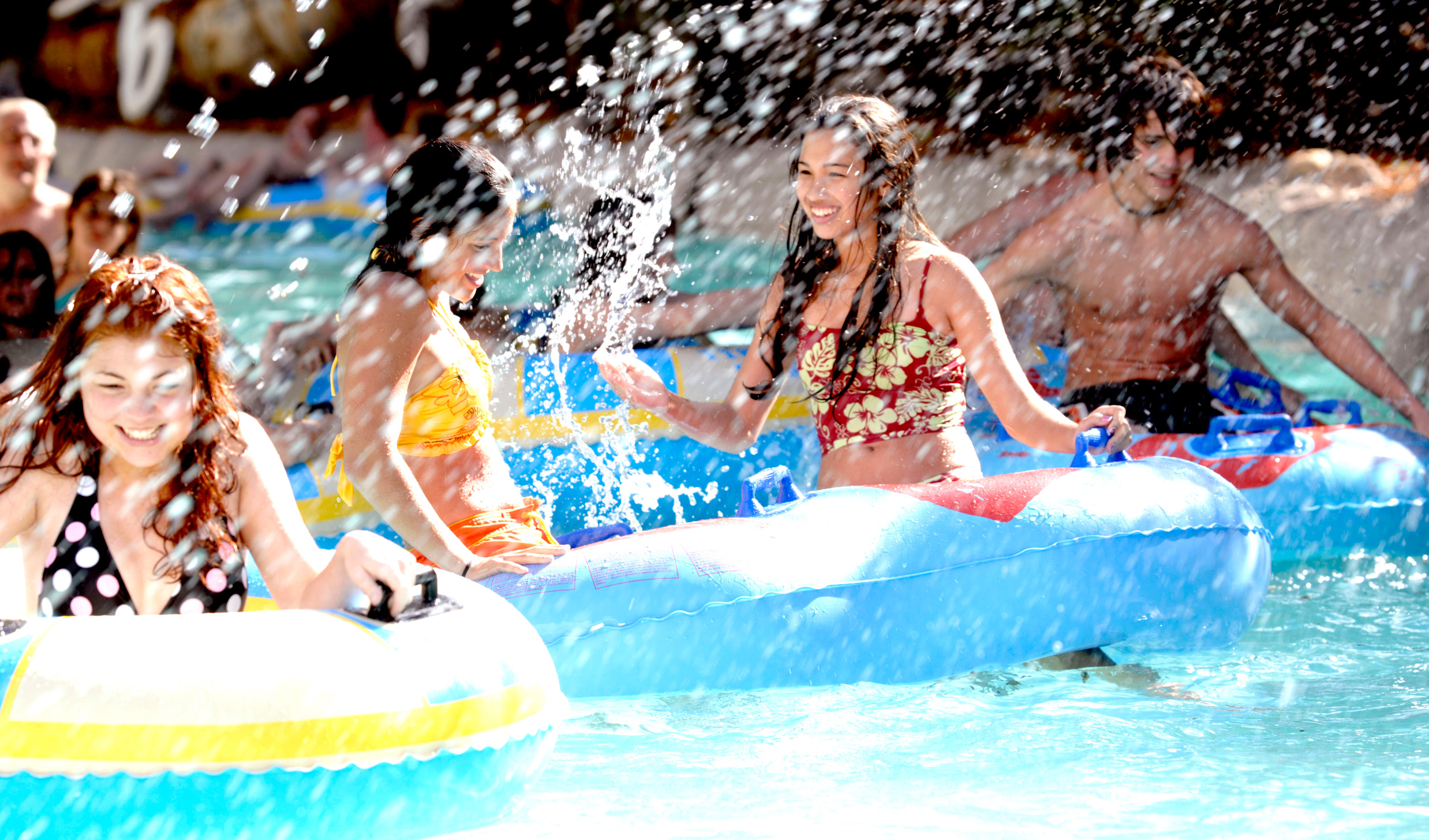 Water splashes about as several young Guests play with inner tubes in the Typhoon Lagoon Surf Pool