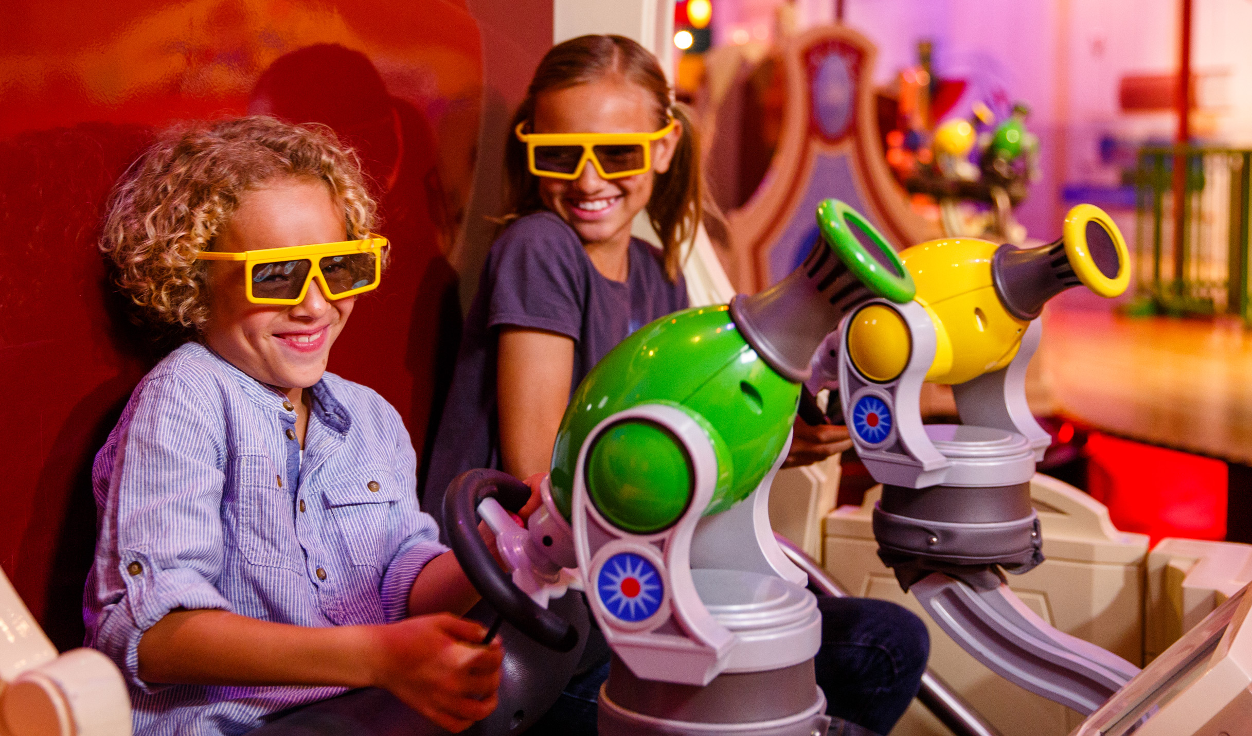 Young Guests wearing 3D glasses smile while they shoot at targets throughout Toy Story Midway Mania!