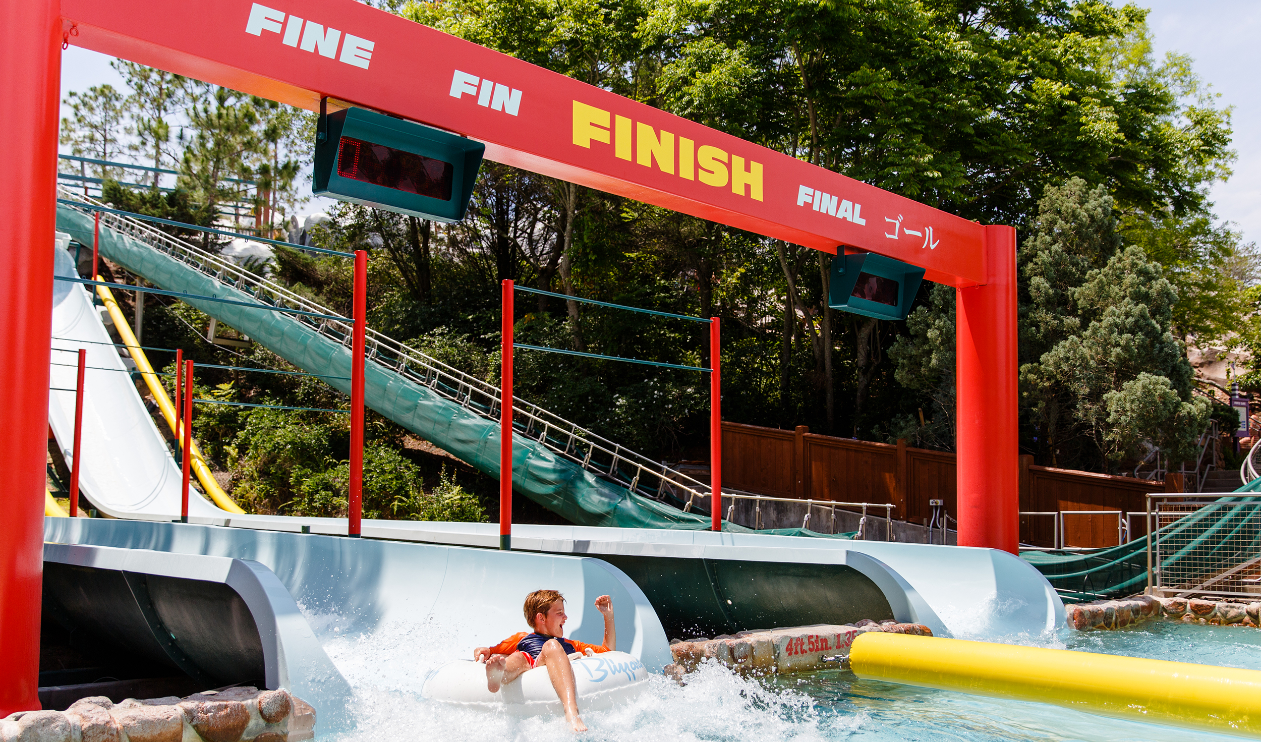 Excited boy on inner tube crosses finish line on the Downhill Double Dipper, a side-by-side waterslide.