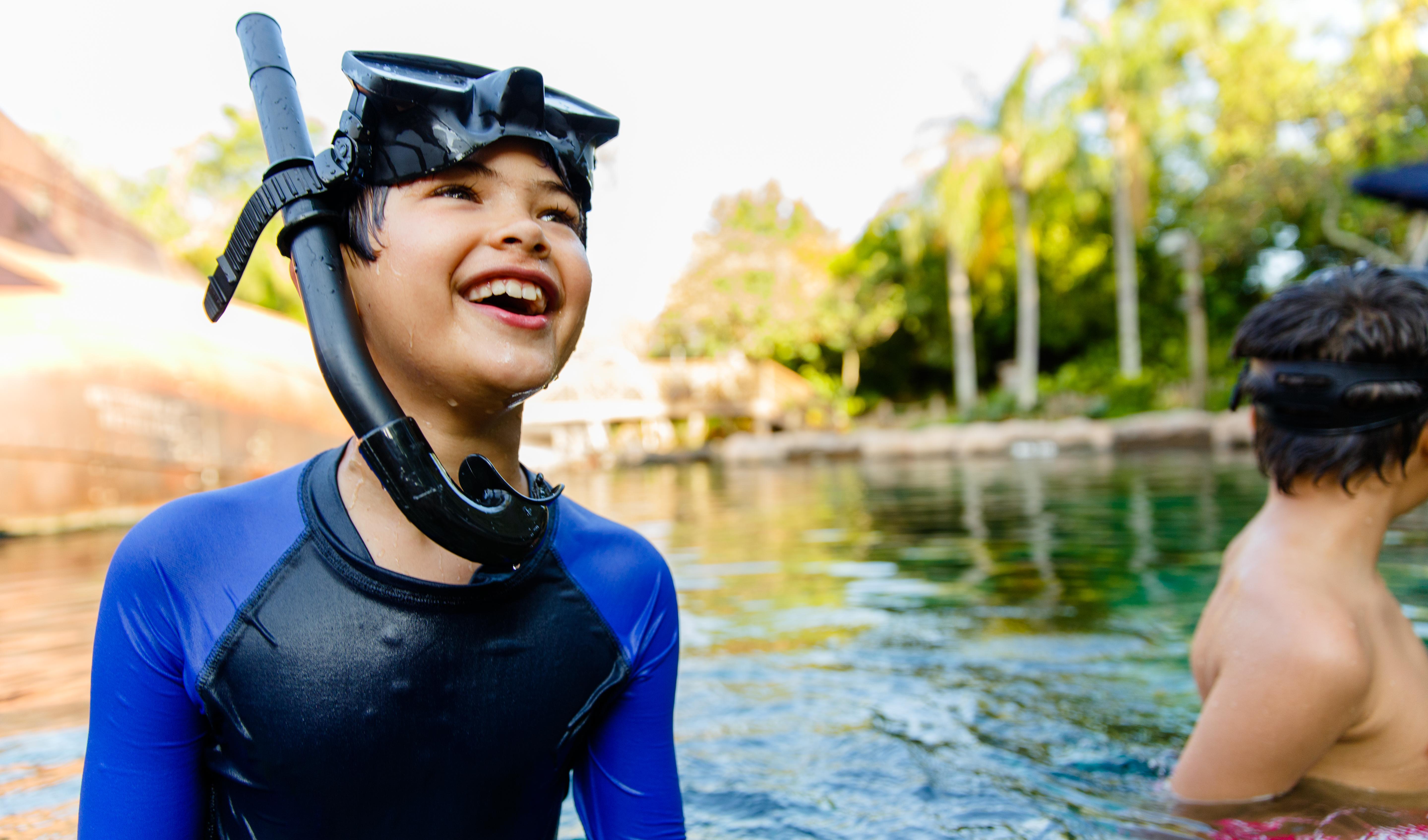 Garoto sorri enquanto usa seu equipamento de mergulho na experiência aquática Shark Reef