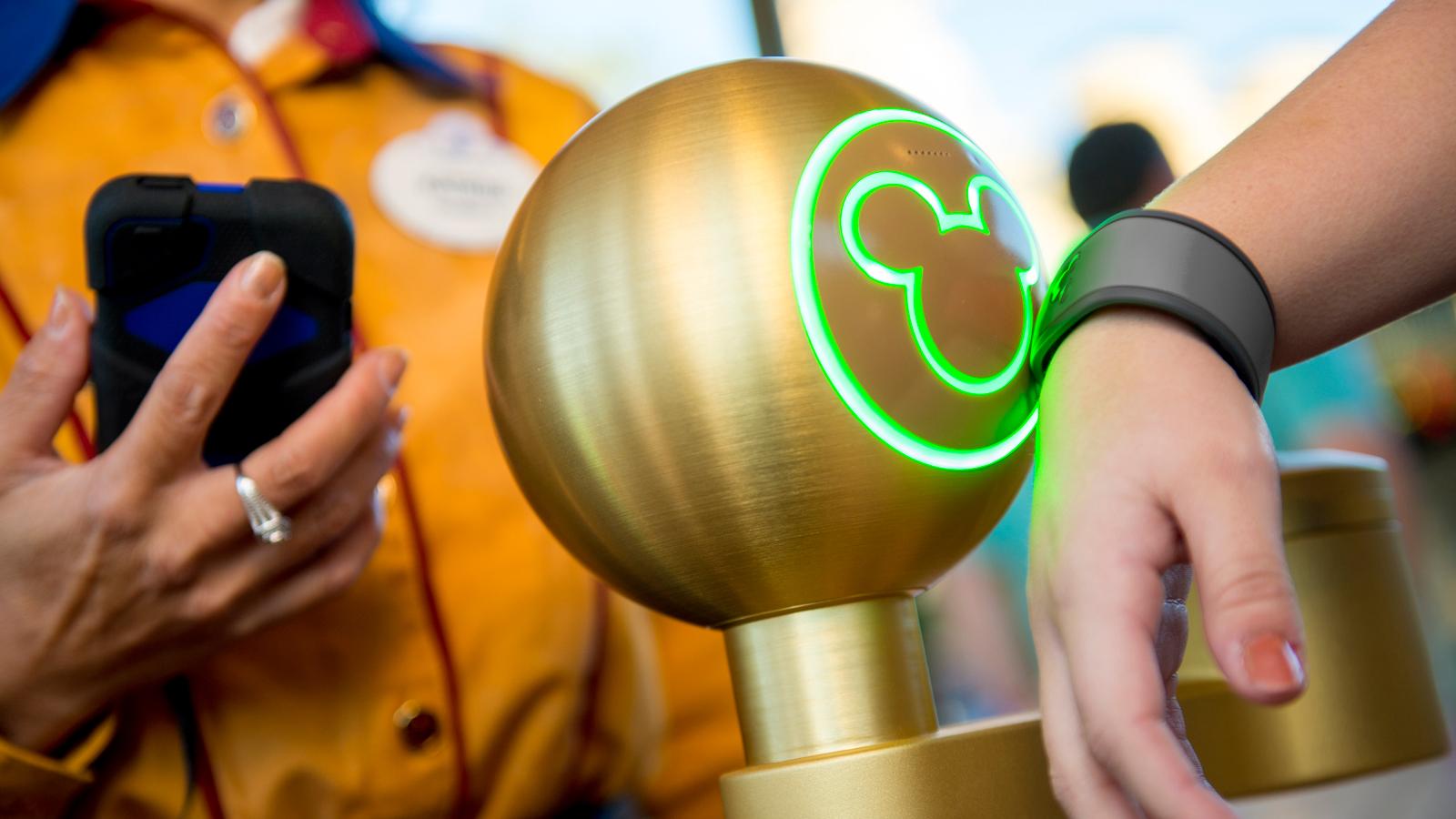 As orelhas do Mickey iluminam, enquanto um visitante colocam uma MagicBand perto de um ponto de toque no Walt Disney World Resort
