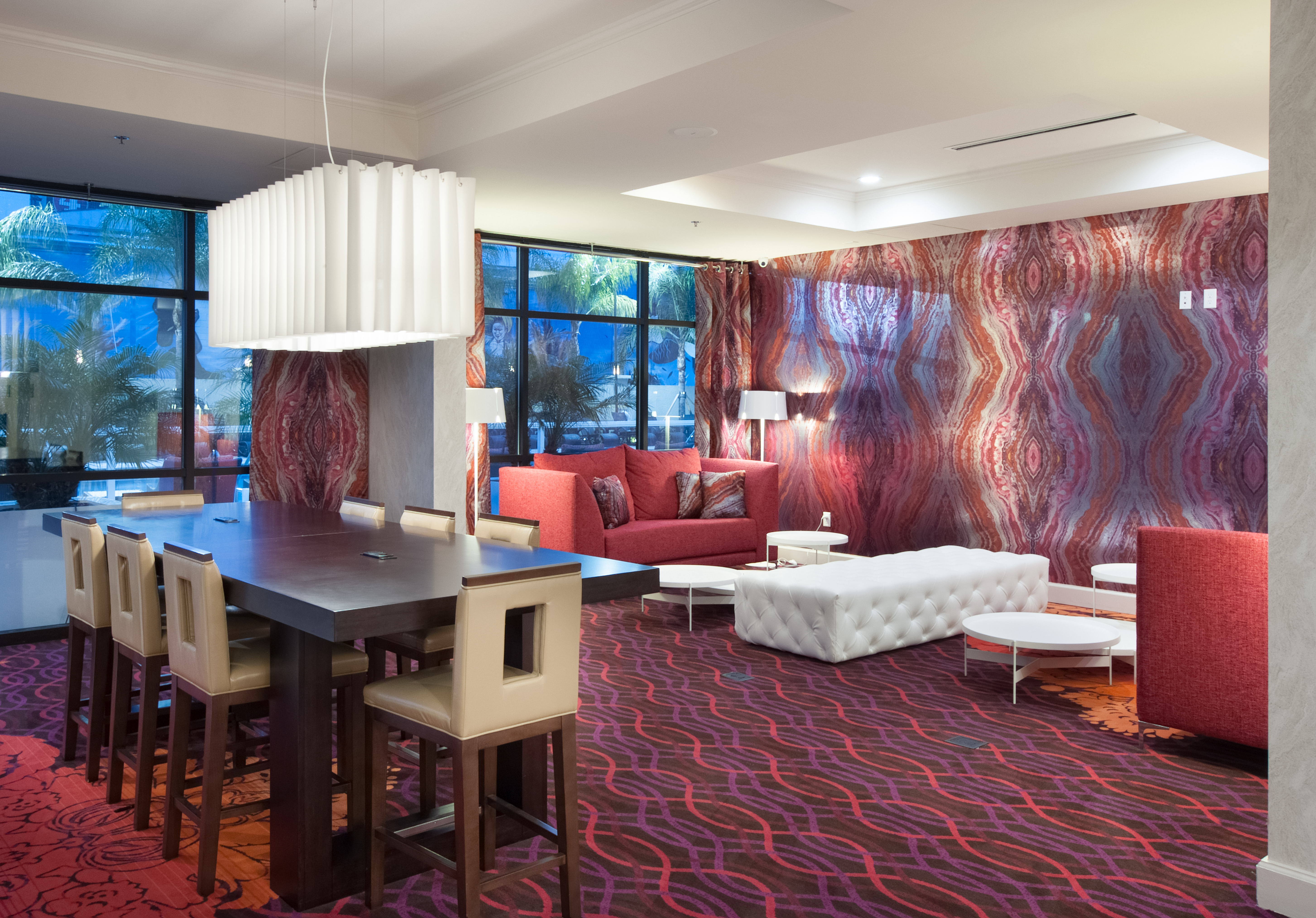 The Contemporary Hotel Lobby Of The Delta Orlando Lake Buena Vista Features  A Hanging Lamp, A Community Table Equipped With Electric Outlets, 2 Floor  Lamps, ...