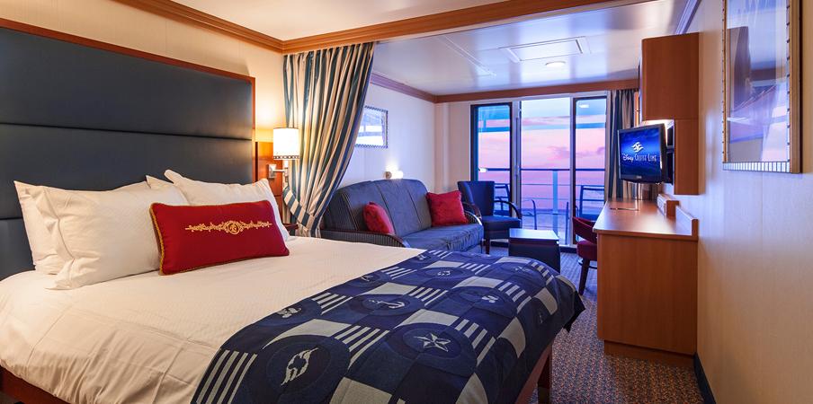 Un camarote con una cama king, sofá, escritorio, sillas y una puerta deslizable de vidrio que lleva al balcón