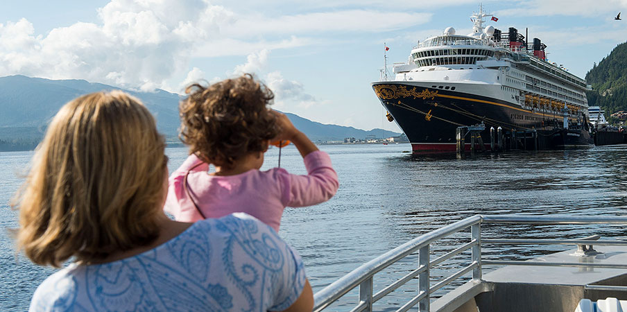 Une femme et une fille regardent un navire de croisière près des montagnes