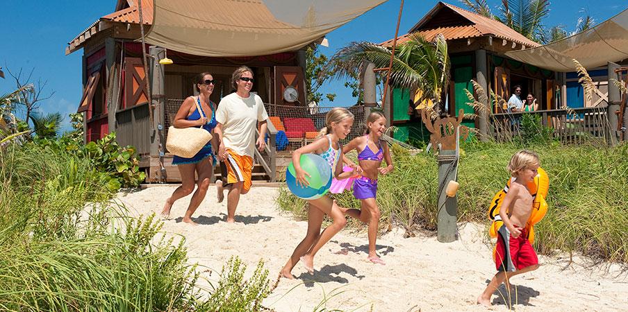 Une famille court sur la plage près des bungalows