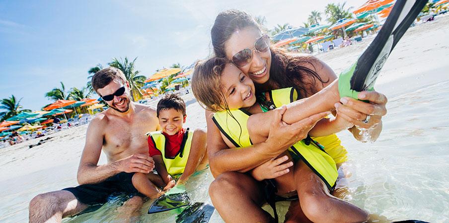 Une famille joue dans l'eau près d'une plage parsemée de parasols et de gens