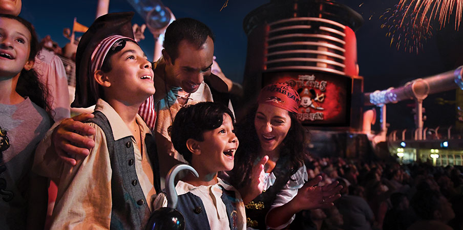 En la fiesta nocturna en cubierta de un barco, una multitud en disfraces de piratas ovacionan el espectáculo de fuegos artificiales