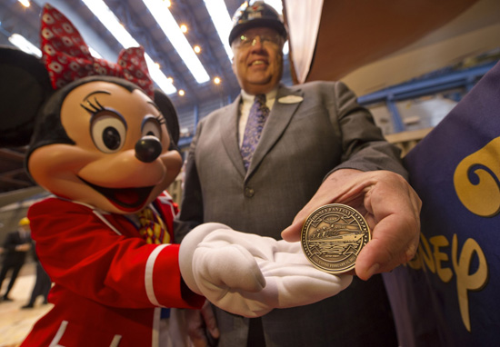 Karl Holz, President of Disney Cruise Line and Minnie Mouse get ready to place the coin in the keel for the Disney Fantasy.