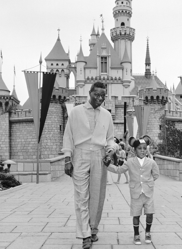 Nat King Cole and His Son, Nat Kelly Cole, in front of Sleeping Beauty Castle at Disneyland Park in 1963.