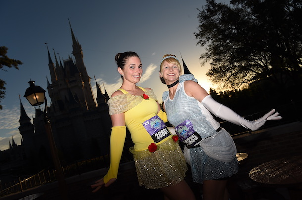 Belle and Cinderella inspired costumes for runDisney marathons pose in front of the Magic Kindgom Park