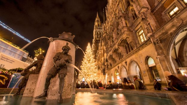 Night image of Munich's glockenspiel with Christmas tree