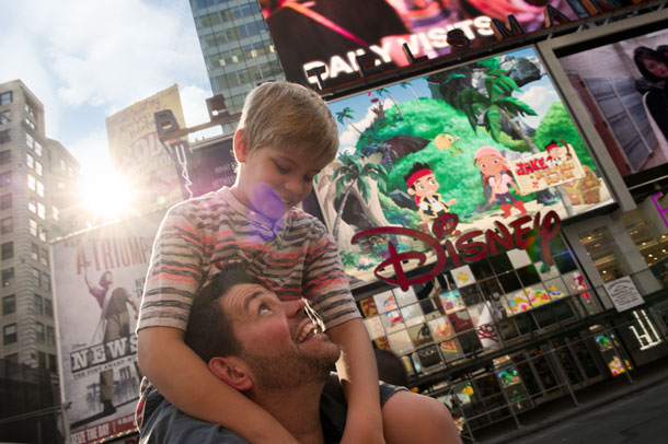 Father with son on shoulders in Times Square on Adventures by Disney New York City vacation