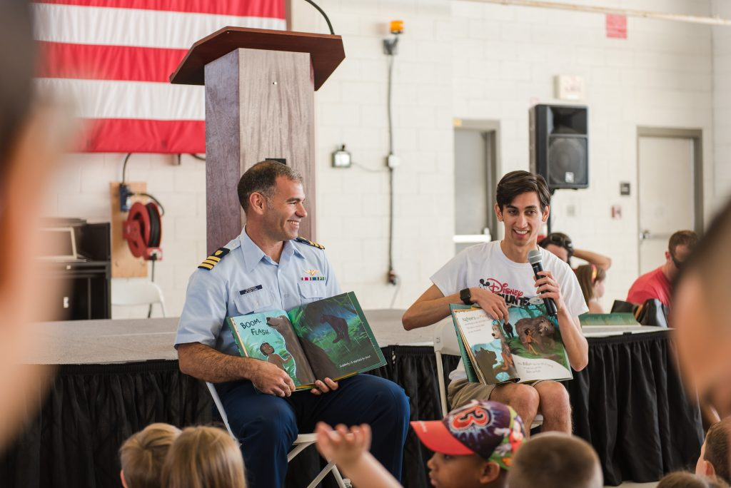 "US Coast Guard Executive Officer, Commander Jeffrey Graham and Disney Cruise Line Entertainment Activities Manager Tim Heidorn are all smiles as they read Mowgli's Rainy Day to children who attended ""Books on Bases."""
