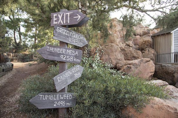 Wooden sign post pointing to the four Big Thunder Mountain Railroad attractions around the world