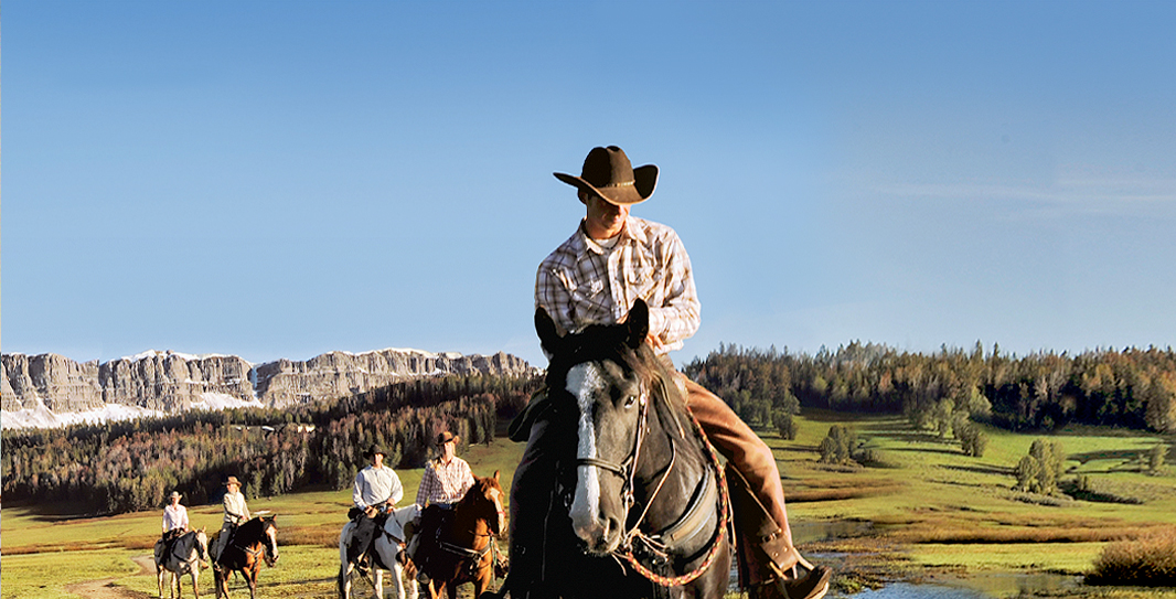 A group wearing cowboy-style clothing ride horses through a grassy valley with a snow-covered mesa behind them