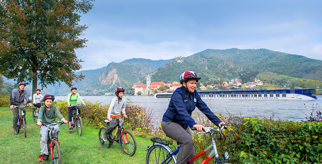 A family riding bicycles along a grassy riverbank as a passenger barge travels the river with a quaint village on the far shore