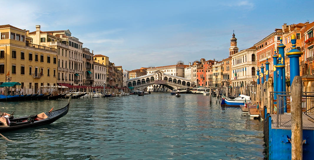In Venice, Italy, a gondola travels along a canal that is flanked by docks and buildings and spanned by a covered bridge