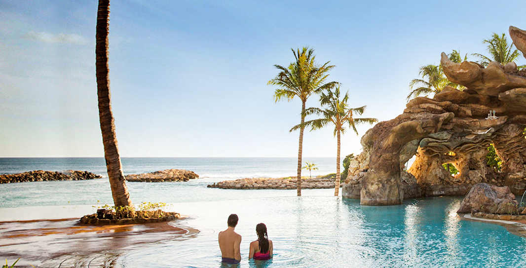 A couple stand waist-deep in Ka Maka Grotto oceanfront pool, looking out into the ocean beyond