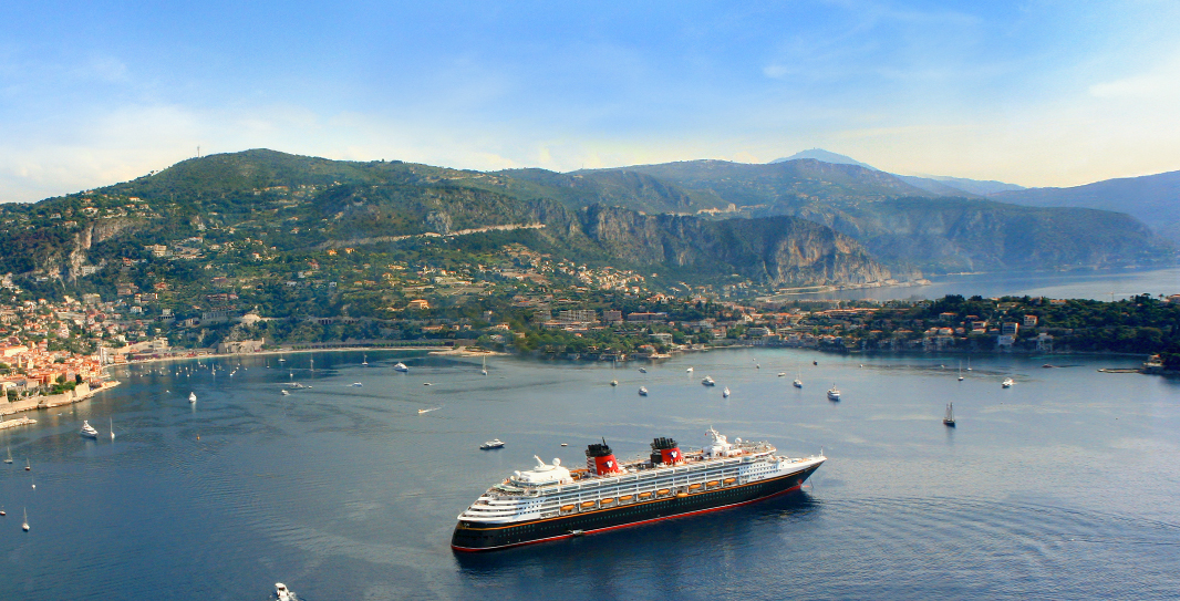 A Disney Cruise Line ship moves past smaller boats in a harbor surrounded by steep hillsides.