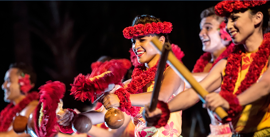 A close up of Hawaiian dancers in leafy skirts, leis and head dresses playing traditional island instruments made of bamboo, coconuts and flowers
