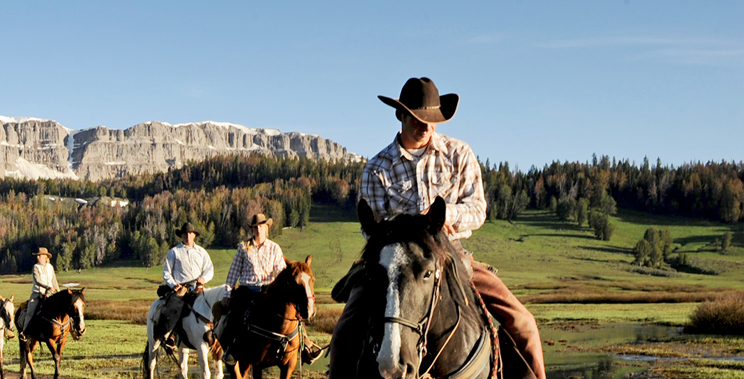 A group wearing cowboy-style clothing ride horses across a grassy valley with a snow-covered mesa behind them